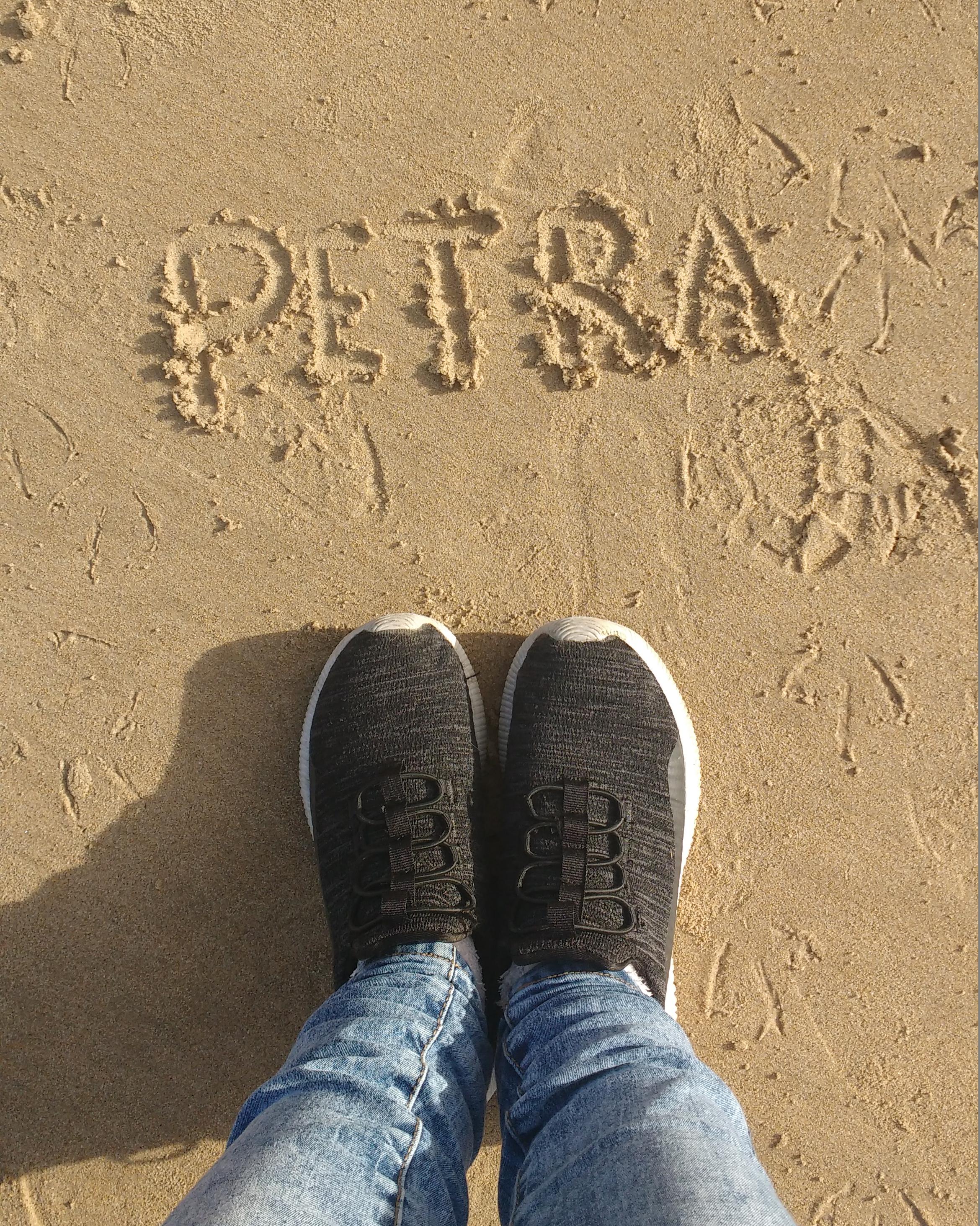 Aparece el nombre de PETRA dibujado en la arena de la playa en mayúsculas. Se ven unas zapatillas negras justo debajo y parte de unos vaqueros. Esta foto la sacó Sonia en Asturias hace casi dos años.